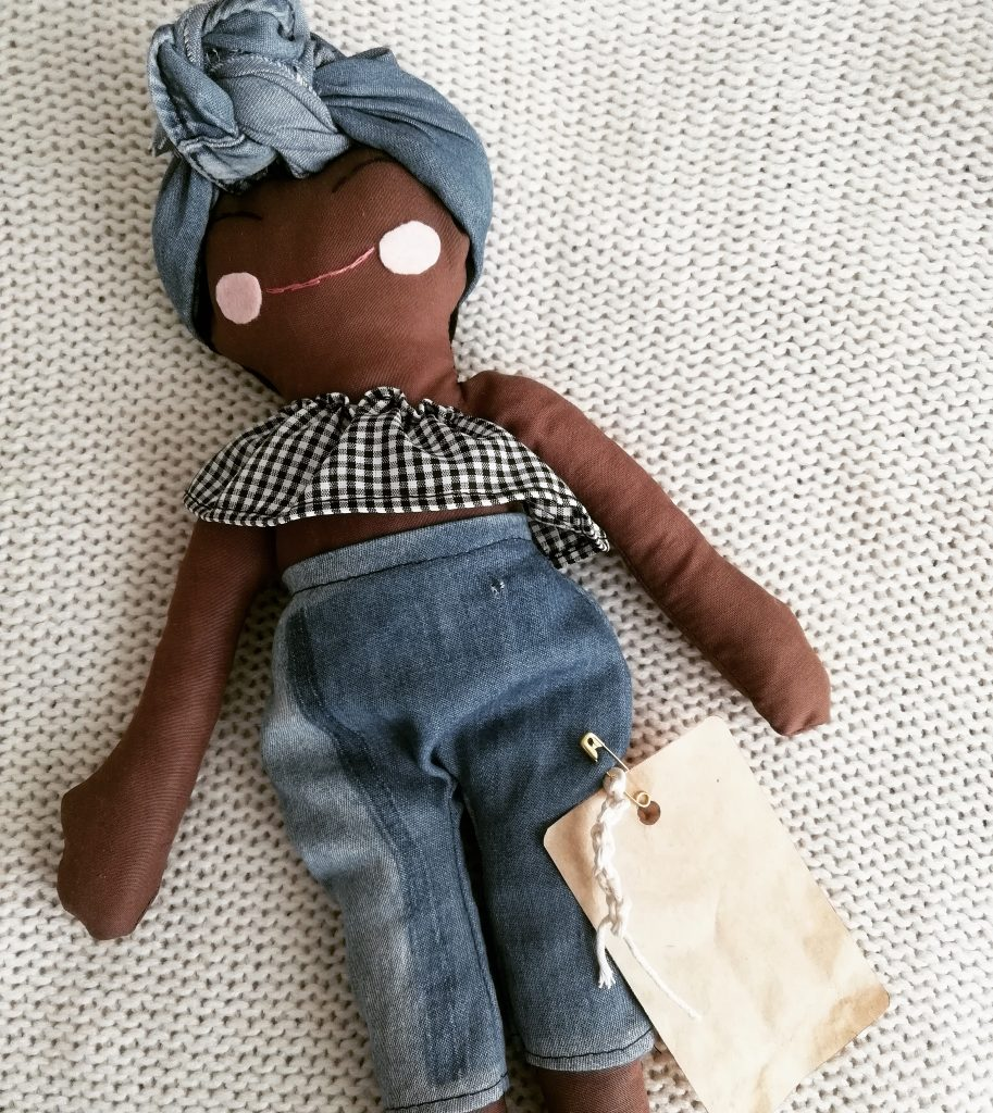 brown doll wearing a denim pant and frill top
